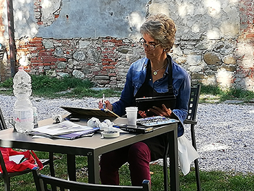 Artist painting during our art workshop in Tuscany open to all levels and media