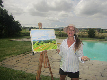 Artist showing her painting during our art workshop offered every June and October in Italy