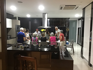 Group of people in a kitchen attending a cooking demonstation during Walk the Arts food tour in South America