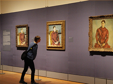 Woman in front of paintings by Cézanne at the Metropolitan Art Museum during Walk the Arts bus trip to NYC from Ottawa and Kingston