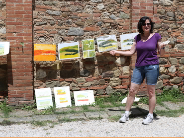 Artist in front of her paintings during our plein air painting workshop in Tuscany