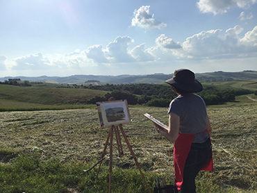 Woman in front of an easel painting the landscape during Walk the Arts art retreat in Italy and painting holidays in Tuscany
